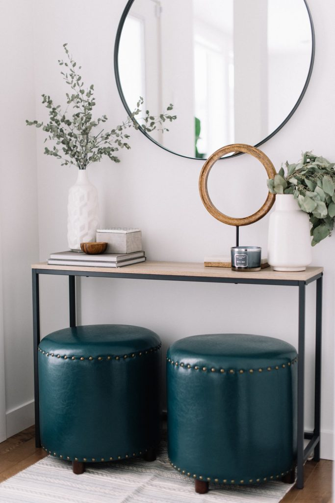 RE-CREATE THE LOOK: 5 MINIMAL OVERSIZED ROUND MIRROR ENTRYWAYS. Hey, Djangles. heydjangles.com. Modern contemporary entryway, round mirror entryway, black round mirror, industrial console, studded foot stools. Photo credit: 204Park.