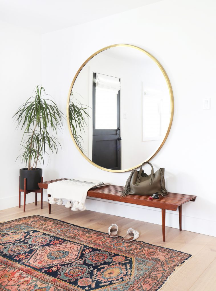 RE-CREATE THE LOOK: 5 MINIMAL OVERSIZED ROUND MIRROR ENTRYWAYS. Hey, Djangles. heydjangles.com. Mid-century modern entryway, round mirror entryway, Bohemian entryway, Tribal/bohemian area rug, gold round mirror, mid-century planter stand, mid-century bench. Photo credit: Amber Interior Design.