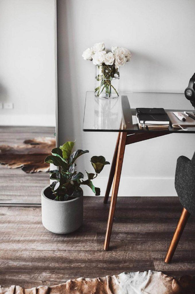 5 MINIMALIST HOME OFFICE WORKSPACE PRODUCTIVITY BOOSTING TIPS – Hey, Djangles. heydjangles.com. Mid-century modern glass desk with vase of flowers, home office desk plant, minimal desk accessories, fiddle leaf fig. Image via Homes to Love. #minimalistdecor #minimalism #homeofficeinspiration