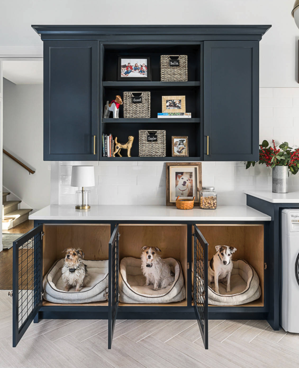 NON-NEGOTIABLE DOG ROOM DECOR ESSENTIALS – heydjangles.com – From dog bowls, pet beds, toys and tech, to pet gates, crates, dog doors and more. Check out our dog room decor wrap-up for all the best dog room decorating ideas and inspiration. Laundry built-in dog crates, blue laundry cabinets. Photo credit: M House Development via Houzz.
