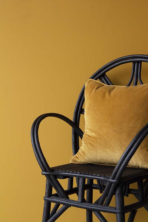Decorating With Mustard Yellow - heydjangles.com - Can't go wrong pairing mustard yellow and black! Mustard walls with black accents, love the black bamboo chair and velvet cushion combo. Image by Rockett St George. #mustardyellow #decorideas #mustardaesthetic