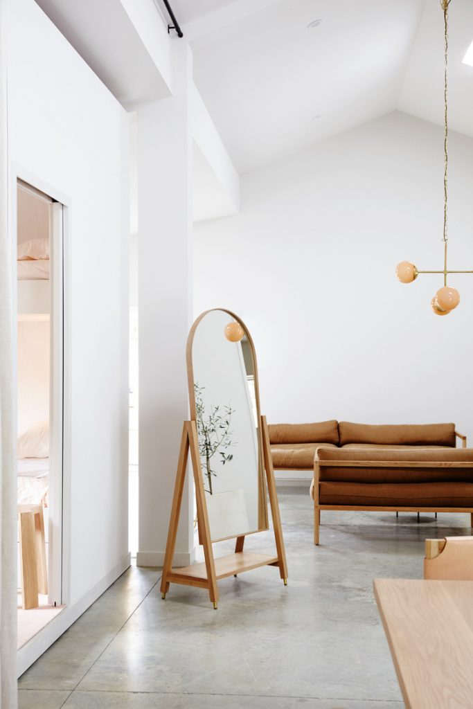 Decorating With Mustard Yellow - heydjangles.com - White walls and tan/mustard accents, tan couch, mid-century statement pendant, arch free-standing mirror. Image by Pippa Drummond. #minimalistlivingroom #minimalism
