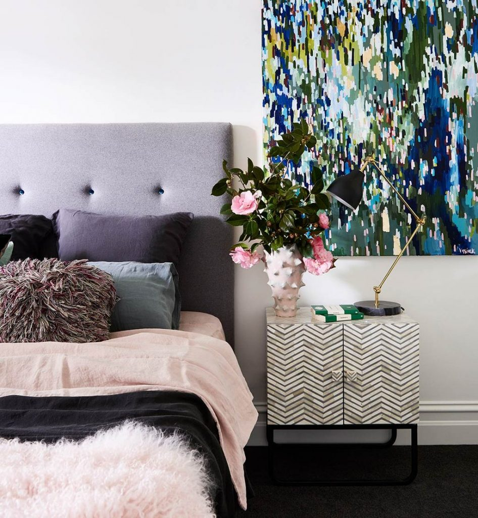 8 KEY ELEMENTS TO A MODERN & EFFORTLESSLY ECLECTIC BEDROOM - heydjangles.com - Element 7 - Beautiful blooms. Oversized abstract artwork, modern bedroom, tufted gray headboard, geometric sidetable, black and brass swing arm lamp. Image via: Fenton & Fenton