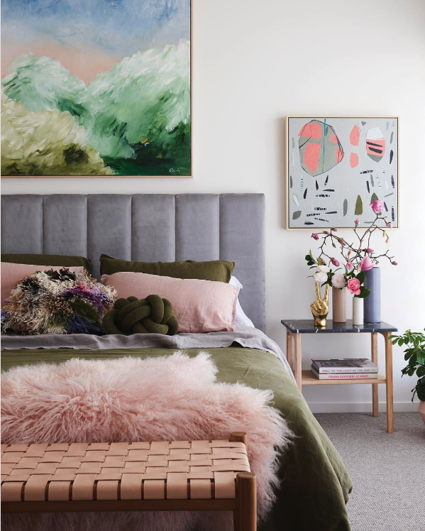 8 KEY ELEMENTS TO A MODERN & EFFORTLESSLY ECLECTIC BEDROOM - heydjangles.com - Element 3 - A footstool or bench at the end of the bench. Oversized wall art, modern bedroom, eclectic decor, olive green duvet, pink woven bench, brass hand peace sign, gray padded headboard, abstract wall art. Image via: Fenton & Fenton