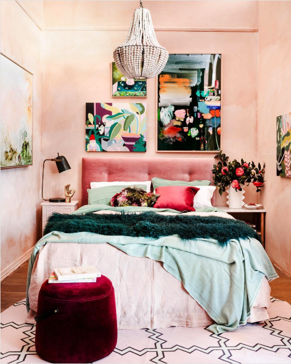 8 KEY ELEMENTS TO A MODERN & EFFORTLESSLY ECLECTIC BEDROOM - heydjangles.com - Element 5 - A throw blanket. Abstract wall art, pink bedroom, eclectic decor, pink and teal bedroom, white beaded chandelier, boho vibes, crimson red velvet round ottoman footstool. Image via: Fenton & Fenton