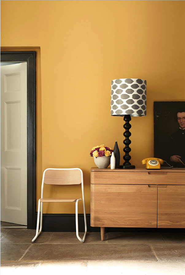 Decorating With Mustard Yellow - heydjangles.com - Can't go wrong pairing mustard yellow and black! Mustard walls with black accents, love the mid-century vibes of this hallway, retro telephone and black trim. Image by Designerpaint. #mustardyellow #retrodecor #mustardaesthetic