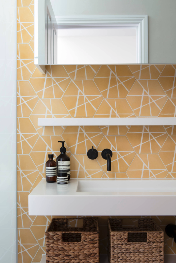 Decorating With Mustard Yellow - heydjangles.com - Mustard yellow hexagonal tiles, geometric tile bathroom splash back, Aesop, matte black faucet and tap, mustard yellow bathroom. Image by Nathalie Priem for Finkernagel Ross Architects. #bathroomideas #mustardaesthetic