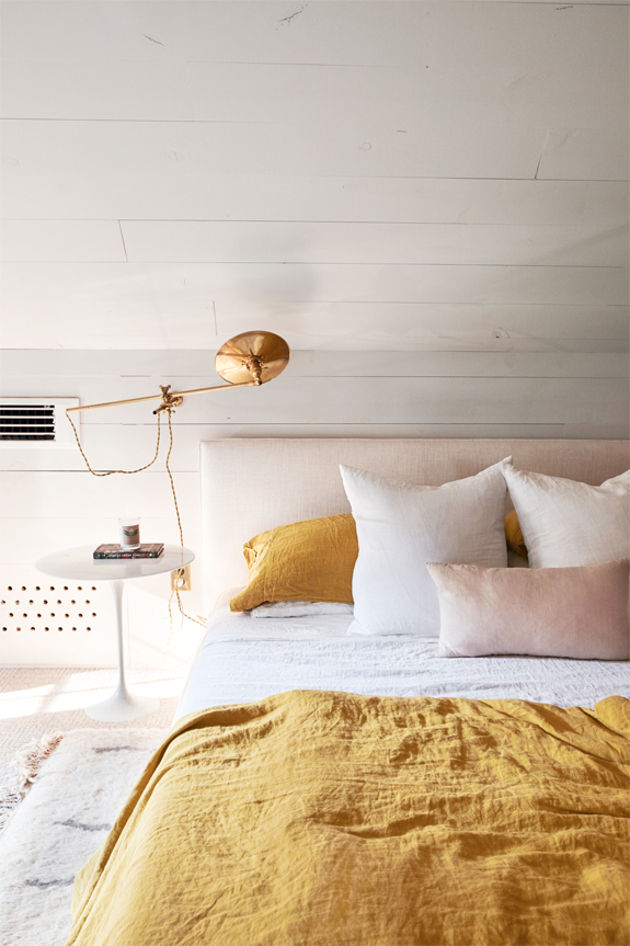 Decorating With Mustard Yellow - heydjangles.com - Mustard yellow and pink bedroom with white walls, mustard linen bedding and pale pink headboard, brass scone light and white bedside table. Looks so inviting! Image by Pippa Drummond Photography. #bedroomdecor #bedroomideas #mustardaesthetic