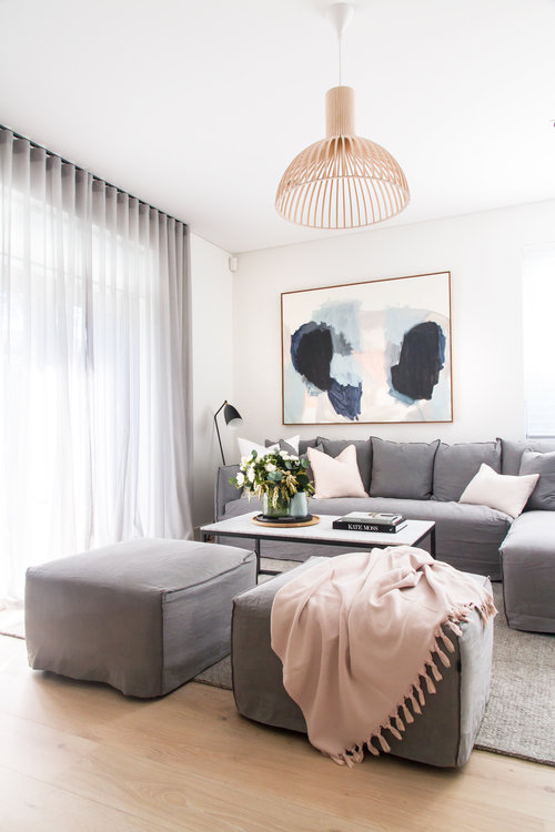 ROUND-UP: Affordable Modern Wooden Pendant Lights - heydjangles.com - Modern white Scandinavian living room, gray and pink living room, gray sofa, pink accents, statement wooden pendant light. Image via The Stables.