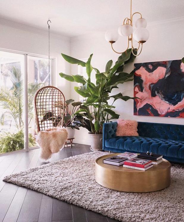 THE GOLD ROUND COFFEE TABLE - 12 STYLISH OPTION - heydjangles.com - round gold coffee table, round coffee table decor ideas, blue velvet sofa, oversize wall art, house plants, modern boho living room. Image via Insta @chelsaeanne