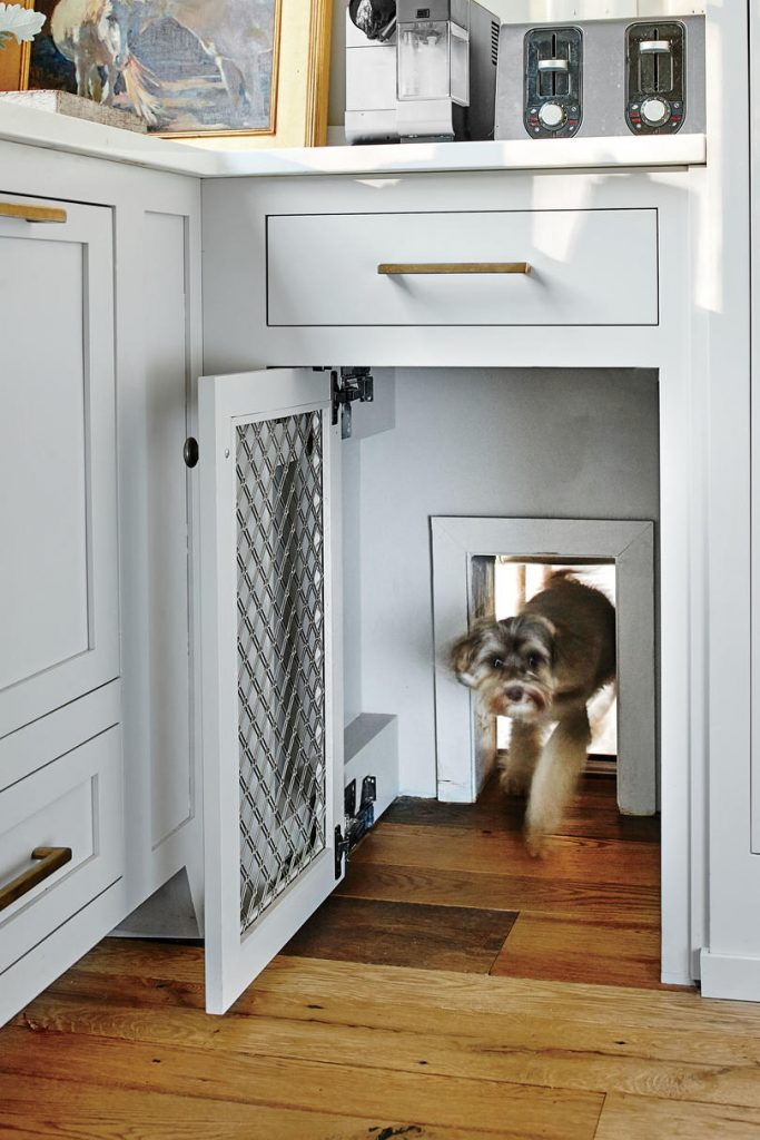 25+ STYLISH DOG DOOR IDEAS FOR THE DISCERNING PET OWNER - Hey, Djangles. Hidden dog door in kitchen cabinet, wall mount dog door, pet door ideas, kitchen pet door, modern farmhouse white and gray kitchen. Image: Laurey W. Glenn.